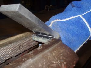 Weld test backing bar removal.