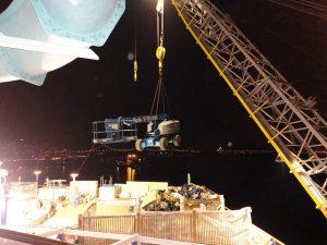 Crane loading a Genie S-65 aerial lift