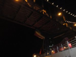 Carnival Spirit passing under the Golden Gate Bridge at night.